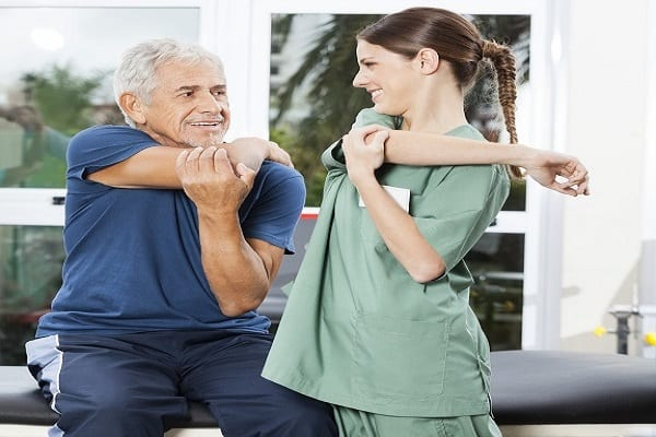 Nurse Guiding Senior Patient In Arm Exercise At Rehab Center